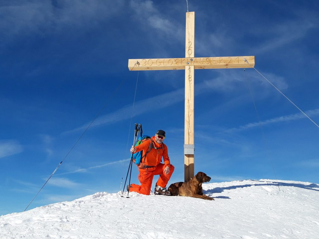 peter mueller mit dem hund am verschneiten gipfelkreuz